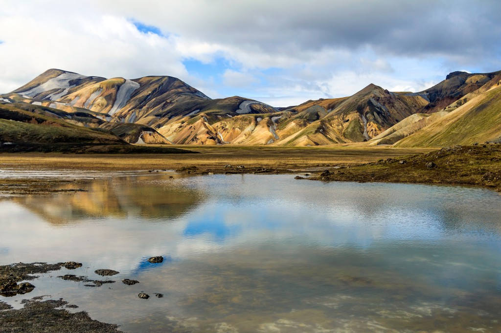 The rainbow rock of Landmannalaugar is reflected in a still lake under a cloudy sky in Iceland