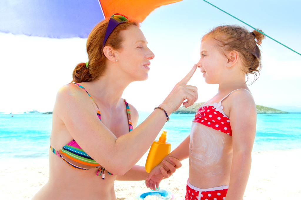 Daughter and mother in beach with sunscreen_94299556