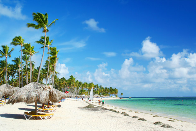 Palapas and beds along white sand beach and turquoise water in Punta Cana