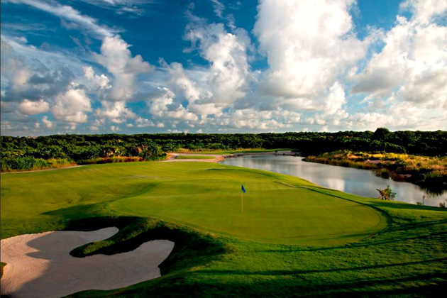 Green golf course with water in background: golf in Punta Cana travel