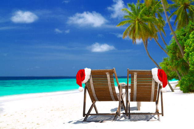 Two chairs on beach with Santa hats on side of chairs