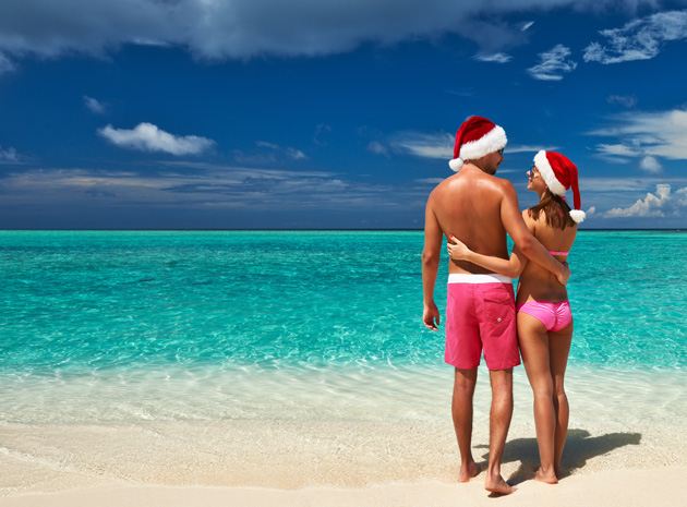 Man and woman in bathing suits and Santa hats stand on beach with turquoise water