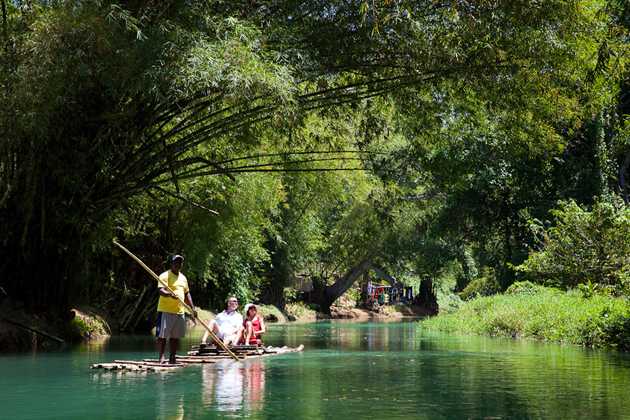 People on raft on green Martha Brae river surrounded by vegetation and trees