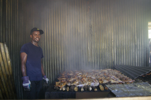 Scotchies jerk chicken hut with cook standing next to meat cooking