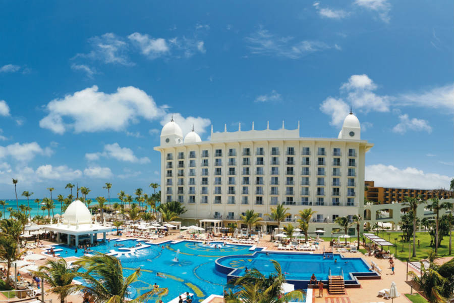 View of large white building of Riu Palace Aruba with pool in foreground