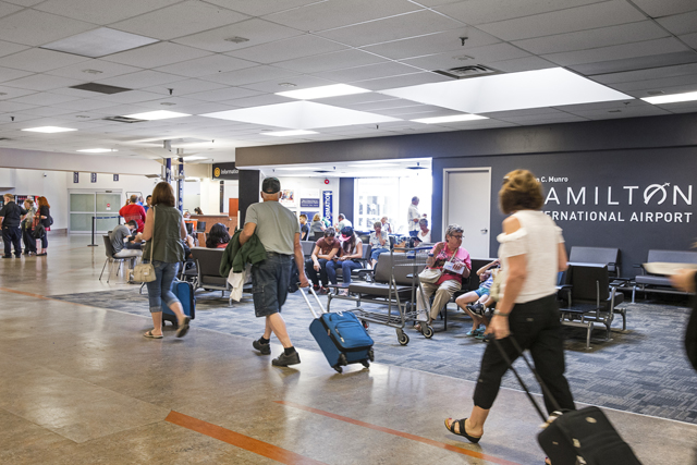 People walk through Hamilton airport pulling suitcases behind them