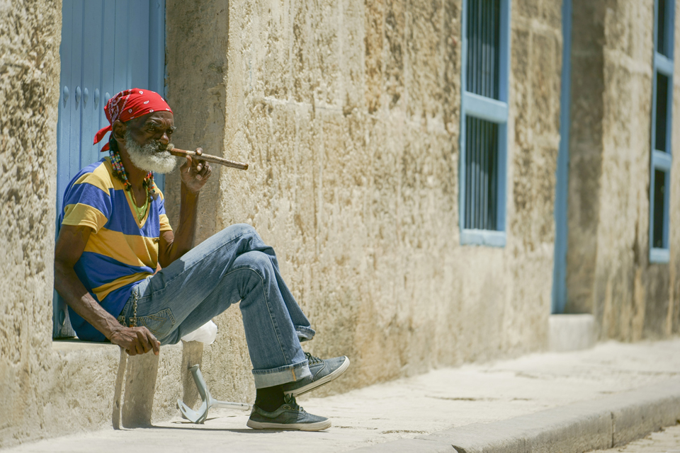 Man sitting outside building smoking cigar in Havana Cuba