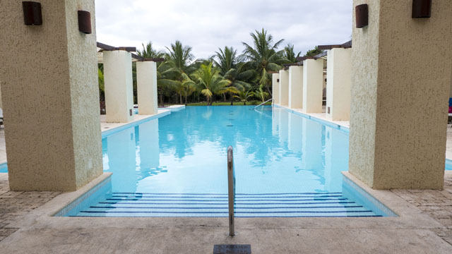 View of pool at Zentropia Spa at the Grand Palladium Resort, with columns lining water.