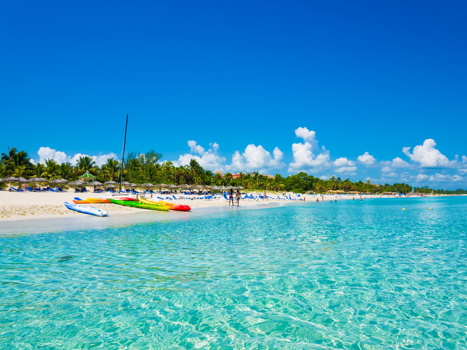 Bright blue water lined with white sand and colourful boats best beaches in Cuba Varadero Beach